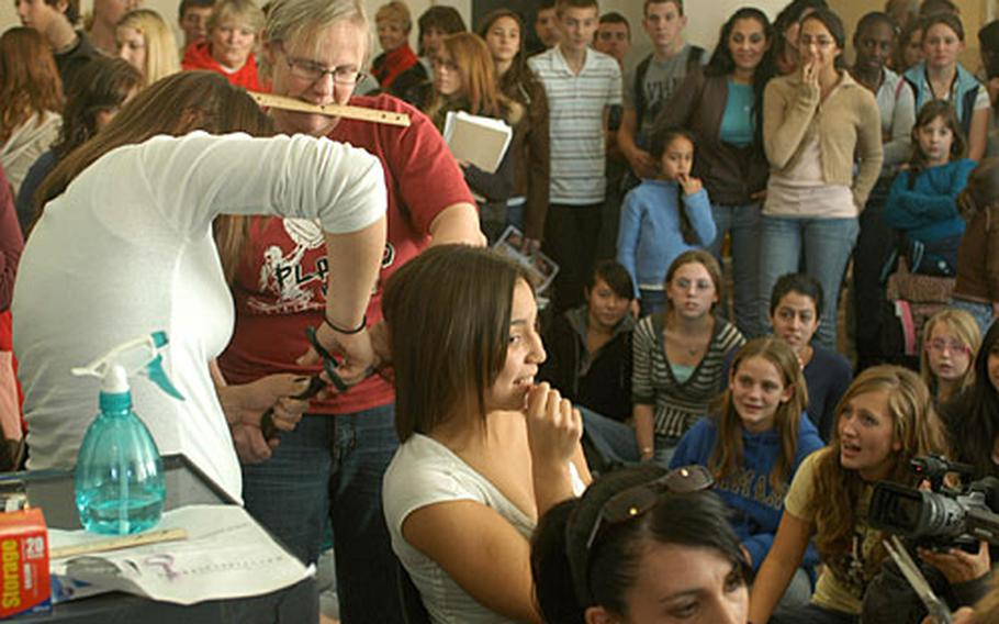 Freshman Krysta Maples loses 10 inches of hair while dozens of fellow students look on at Aviano High School.