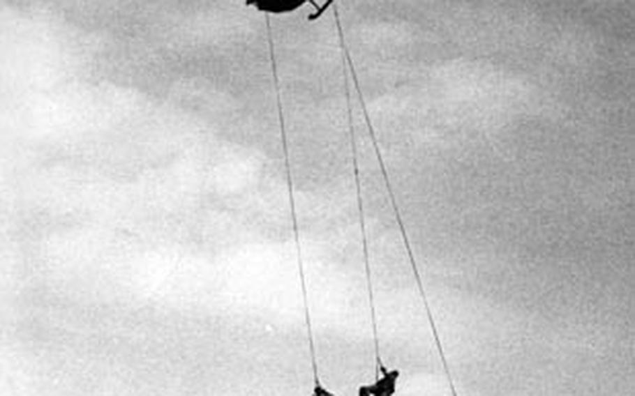 Three U.S. Navy SEALs dangle from helicopter winches after a running takeoff from a Vietnamese beach during a fast-getaway demonstration in 1967.