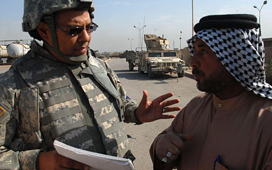 Human Terrain Team member Fouad Lghzaoui, left, talks to Sheik Nouri, who manages a propane distribution station in Baghdad, on Sunday. The team is charged with bringing cultural awareness to the Army.