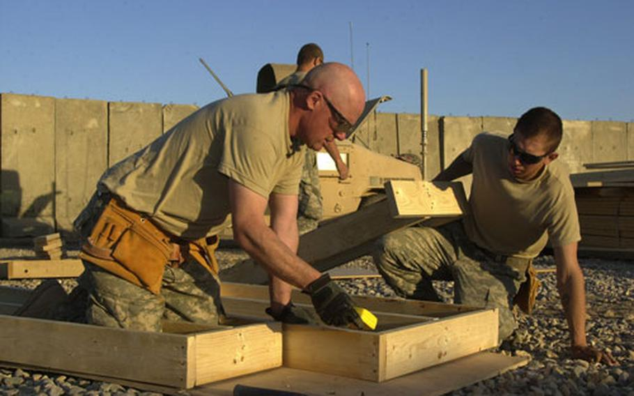 Staff Sgt. Charles Warne, of Glen Willard, Pa., and Spc. Levi Lavalla of Georgia, Vt., build a tower platform at Combat Outpost Salie in Narwan, Iraq. The two joined fellow soldiers from the 8th Battalion, 64th Combat Engineers to help build the base from scratch within 30 days.