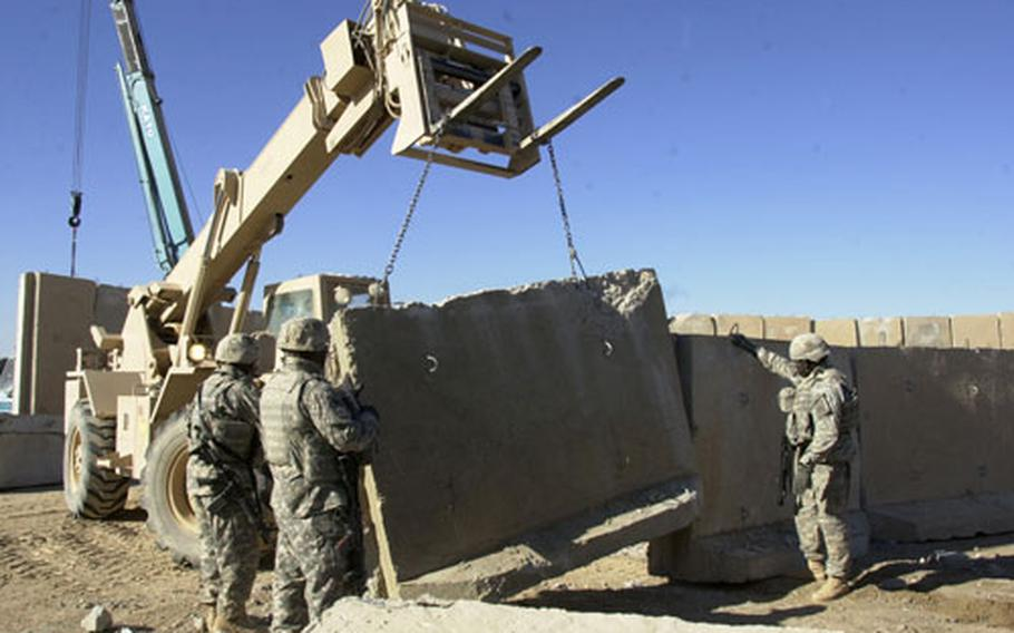 Soldiers help lower concrete barriers in place at Combat Outpost Salie.