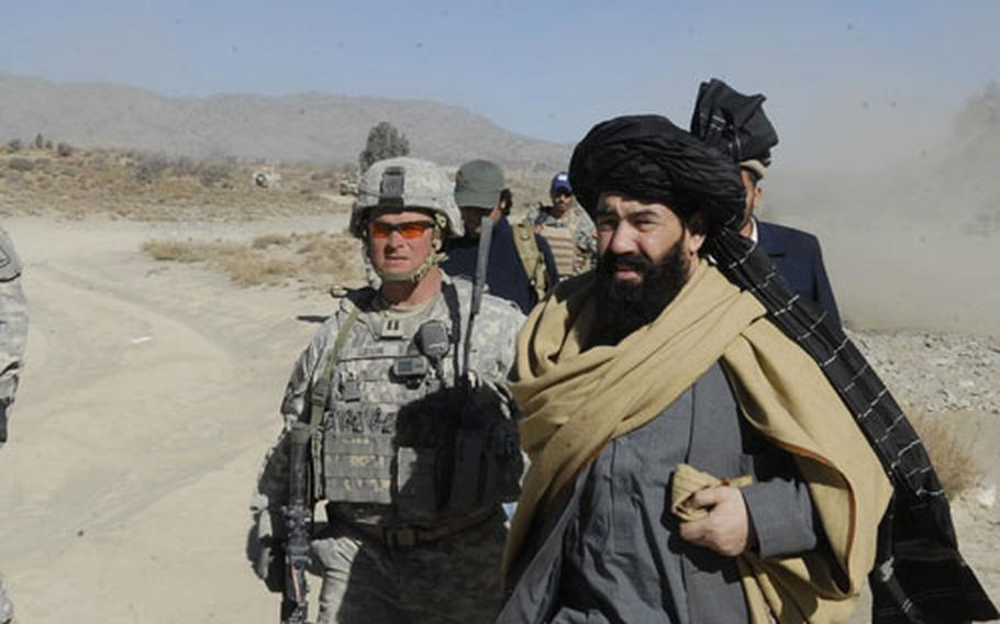 U.S. Army Capt. John Gibson, 30, from Shreveport, La., escorts Afghanistan Paktika provincial parliamentarian Khaled Farouqi off a military helicopter.