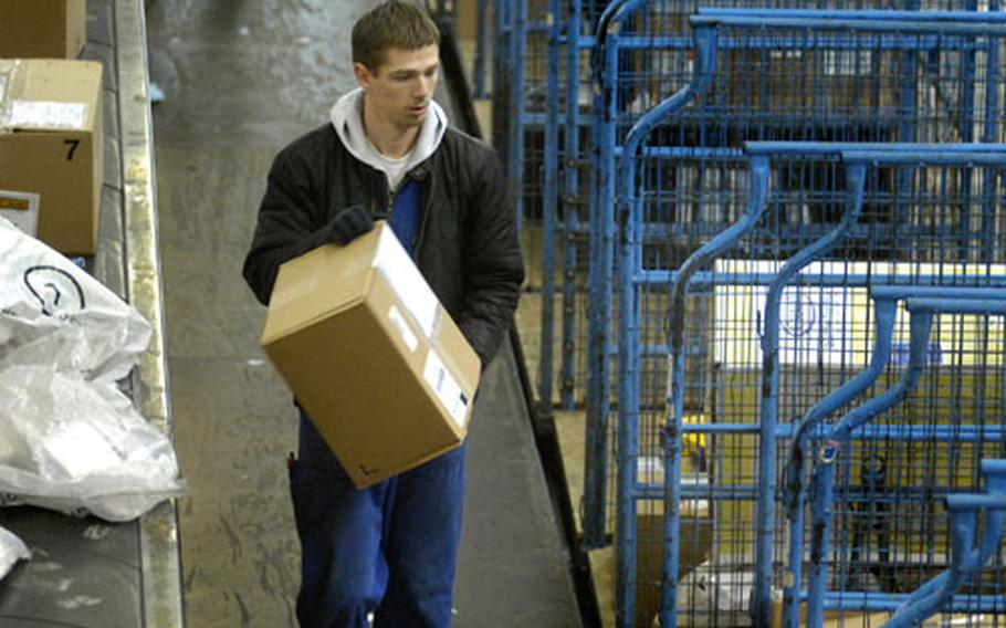 Chris Neumann, a contract mail handler, organizes incoming mail for delivery last week at the mail handling facility in Frankfurt. The volume of mail processed at the facility jumps to some 100 tons a day from mid-December until Christmas.