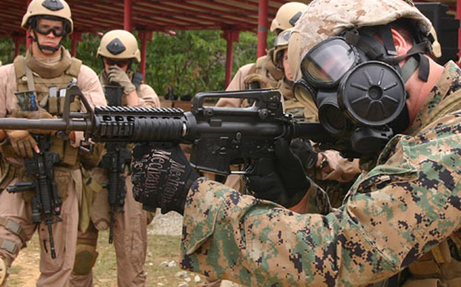 Staff Sgt. Jonathan White, right, 33, from San Antonio, with Special Operations Group, demonstrates to students in the Dynamic Assault Course how to fire an M-4 rifle while wearing a gas mask at Camp Hansen's Range 16.