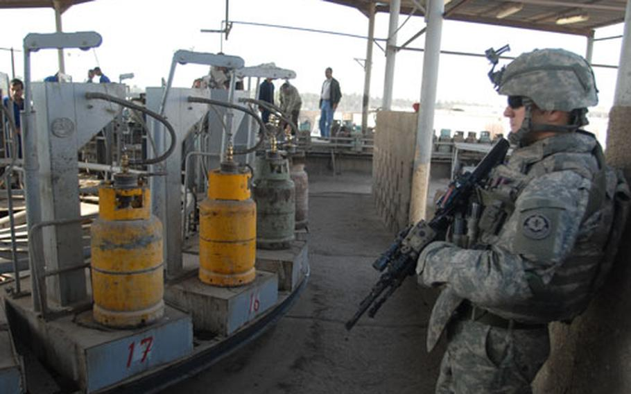 A 2nd Squadron, 2nd Cavalry (Stryker) Regiment soldier checks out the tank filling operation at Sarmoud Propane Station in Baghdad.