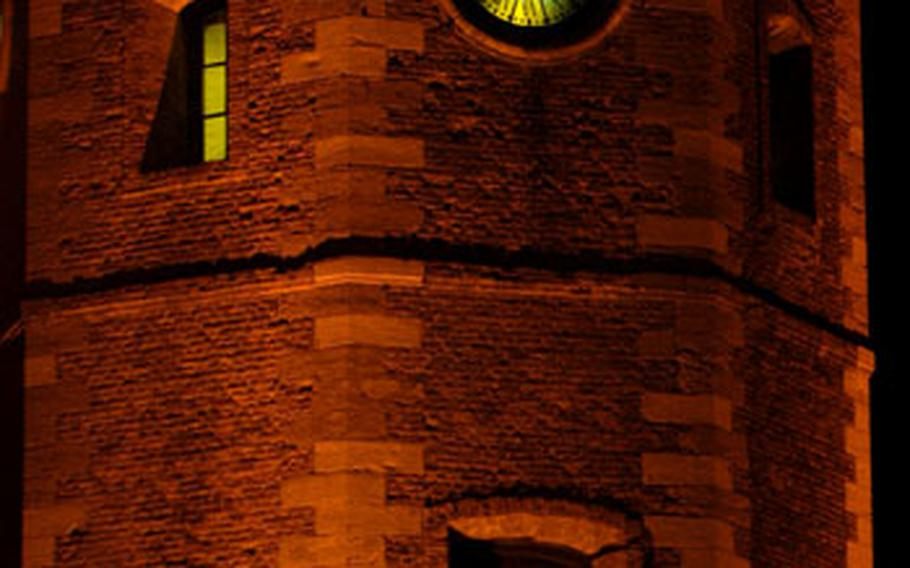 The clock tower in central Dunkirk glows at night.