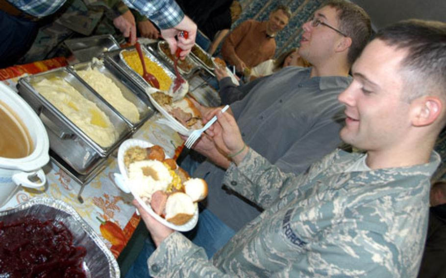 Airman 1st Class Adam Aikens, 23, of Camden, N.Y., reaches the end of a long serving line with a full plate Tuesday evening at Misawa Air Base, Japan. Aikens and other single servicemembers living in the dormitories had an early home-cooked Thanksgiving meal, courtesy of the 373rd Intelligence Group's Senior Enlisted Council and U.S. Navy Information Operations Command's Chief Petty Officer Association. The two groups combined to prepare food for 200 to 300 single airmen, sailors and soldiers at Misawa who work on Security Hill.