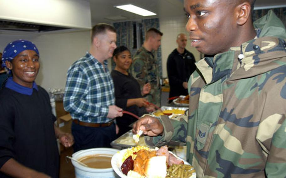 Staff Sgt. Herbert Copemann, 26, loads up his plate with traditional Thanksgiving food Tuesday night at Misawa.