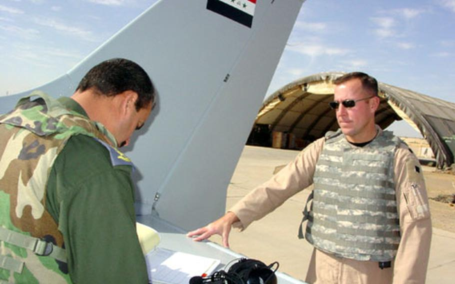 Lt. Col. Mark Bennett, right, commander of the 52nd Expeditionary Flight Training Squadron, and Col. Basim, an Iraqi Air Force instructor pilot, go through pre-flight checks before taking off on a training flight with a Cessna 172 Sunday at Kirkuk Air Base, Iraq. The U.S. Air Force is helping rebuild Iraq's Air Force and last month opened a new flight training school.