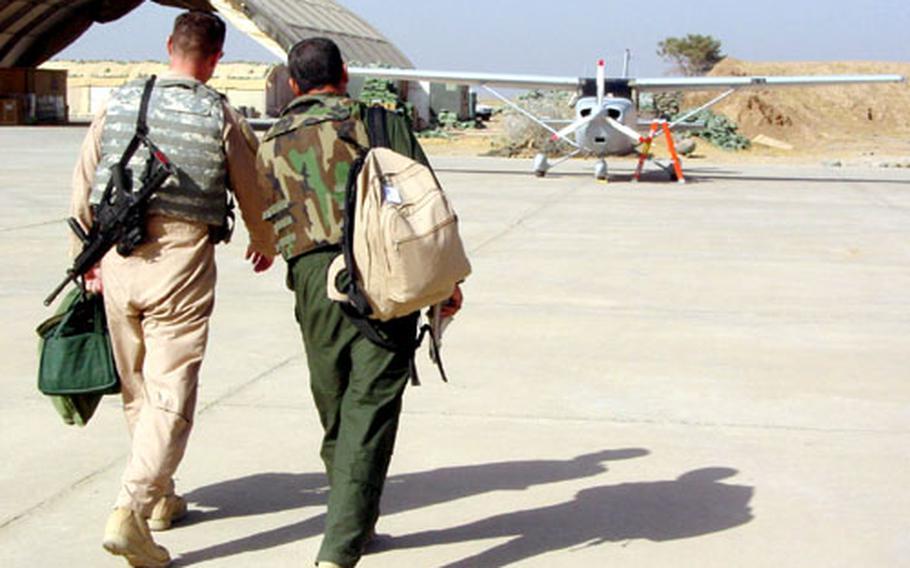 Lt. Col. Mark Bennett and Col. Basim walk toward an Iraqi Air Base Cessna 172 airplane before a training flight.
