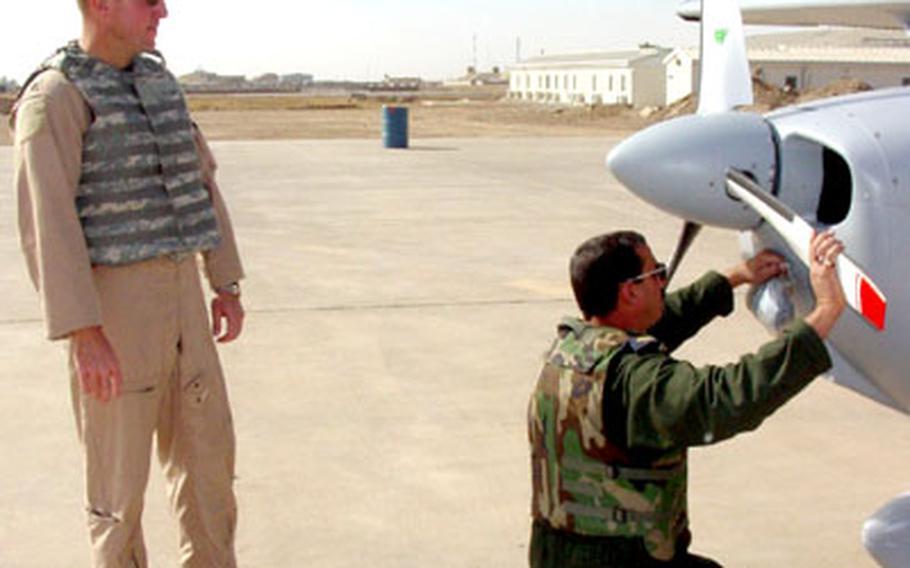 Lt. Col. Mark Bennett watches as Col. Basim checks the propeller on a Cessna 172 before a training flight.