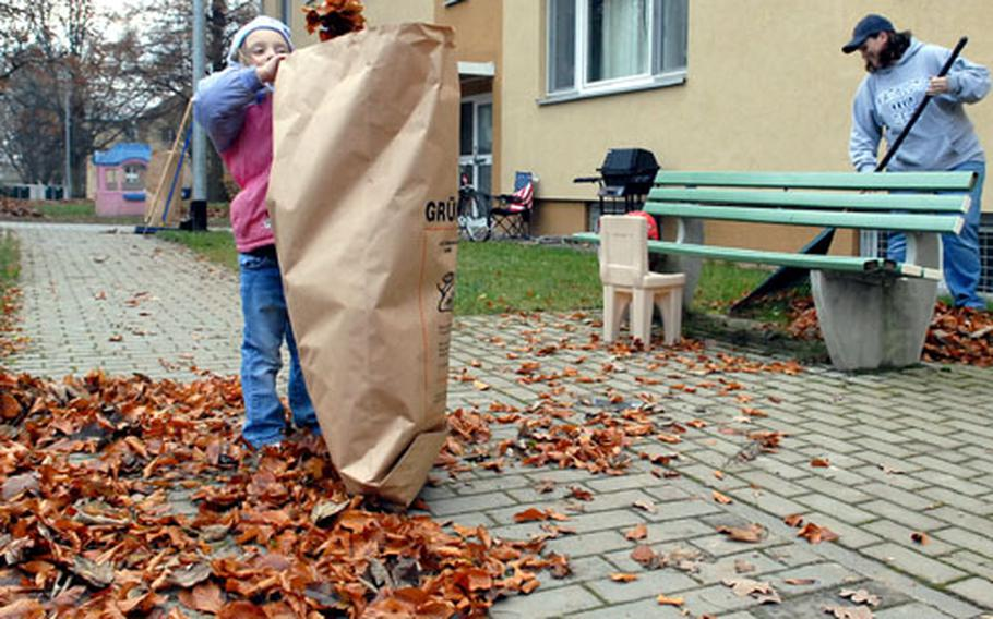 Aimee Duchanse, 4, fills a bag that is almost as tall as she is with leaves, as she helps her mom, Sarah, during the Wiesbaden, Germany, military community's fall cleanup day on Tuesday. The two were tidying up in front of their Hainerberg housing area apartment building.