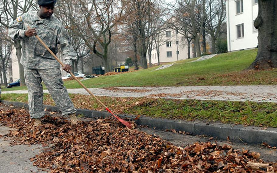 Staff Sgt. Clifton Marshall of the 123rd Main Support Battalion rakes the leaves in the parking lot in front of his Hainerberg housing area apartment building.