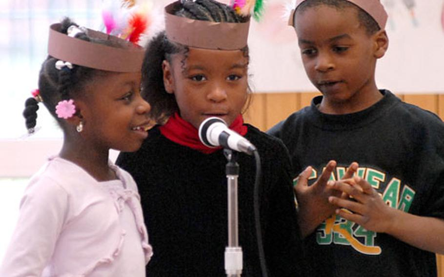 First-graders Brianna Thomas, left, Kina Baird, center, and Deandre Fulmore play the part of Indians at Dexheim Elementary School's Thanksgiving celebration.