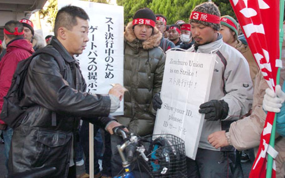 A Japanese base worker shows his identification card to pass through picket lines manned by Zenchuro labor unionists in front of the Yokosuka Naval Base Main Gate. Essential members such as security forces, firemen and hospital workers were allowed on base in spite of the strike.