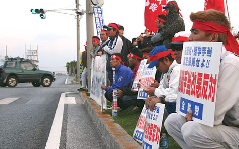 Japanese employees of U.S. military bases line the side of Highway 58 in front of Kadena Air Base's Gate 1 on Wednesday. The strikers turned north toward Tokyo with their backs to Kadena to show that they weren't against the U.S. military, but were protesting the Japanese defense ministry, according to some strike partcipants.