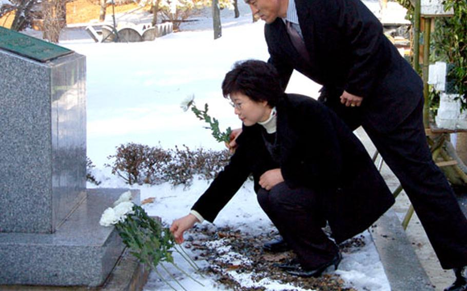 Chang Chun-ki places a flower at the memorial for his brother, Cpl. Jang Myoung-ki, a Korean Augmentee to the U.S. Army who was killed during a firefight in the Joint Security Area on Nov. 23, 1984.