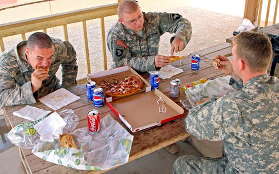 Sgt. William McCormick (left), 24, of Savannah, Tenn., Pfc. Dustin Roscoe, 21, of Burleson, Texas and Capt. Brian Mason (right), 25, of Philadelphia chose sandwiches and pizza over traditional Thanksgiving fare Thursday at Contingency Operating Base Speicher in northern Iraq. They said Thanksgiving was just like any other day in Iraq and saw no particular reason to celebrate. They are with the 0411 Military Transition Team, 1st Brigade, 101st Airborne Division.