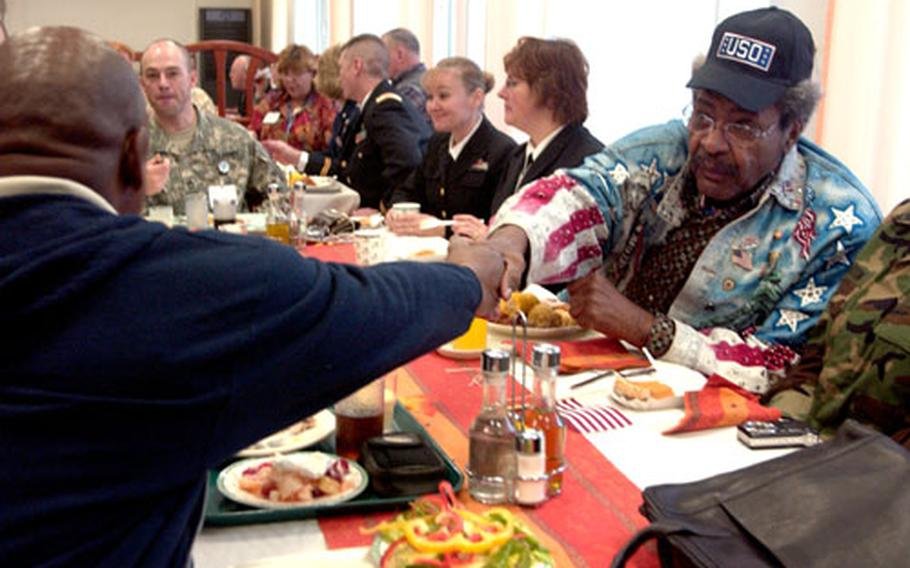 Sgt. Clive Morton, who was recently brought to Landstuhl Regional Medica Center from Iraq, shakes hands with boxing promoter Don King during lunch Thursday. King was visiting the hospital in Germany for the second time through the USO.