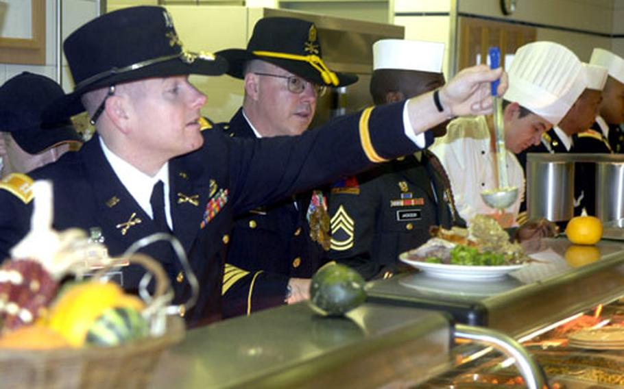 Capt. Jon Paul Hart dishes out food during a Thanksgiving celebration in Baumholder, Germany, home to soldiers of the 2nd Brigade, 1st Armored Division. The brigade, which just completed a round of training in the field, deploys to Iraq early next year.
