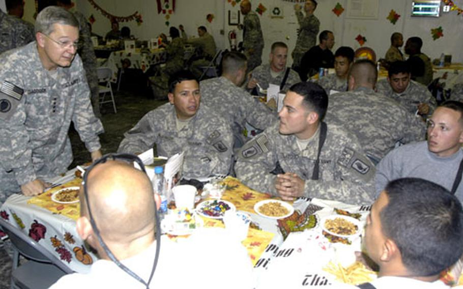 Gen. Bantz J. Craddock, commander of Supreme Headquarters Allied Powers Europe and the U.S. European Command, talks with soldiers during Thanksgiving dinner on Thursday at Forward Operating Base Fenty in Jalabad, Afghanistan. Clockwise from top are Sgt. Robert Maldonado, Sgt. Jaime Velazquez, Pfc. Luis Velez, and Spc. Yariel Roman of the 173rd Airborne Brigade Combat Team, as well as civilian Feliz Rivera.
