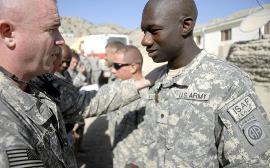 Col. Martin Schweitzer (left), commander of the 82nd Airborne Division's 4th Brigade, congratulates Spc. Samuel Williams, 24, a native of Long Beach, Calif., after pinning the U.S. Army Commendation Medal (with Valor device) on his lapel on Thanksgiving Day in Afghanistan. The award was given for a firefight Williams and several of his fellow soldiers were in September. Williams is a member of Troop C, 4th Squadron, 73rd Cavalry Regiment, 82nd Airborne Division.