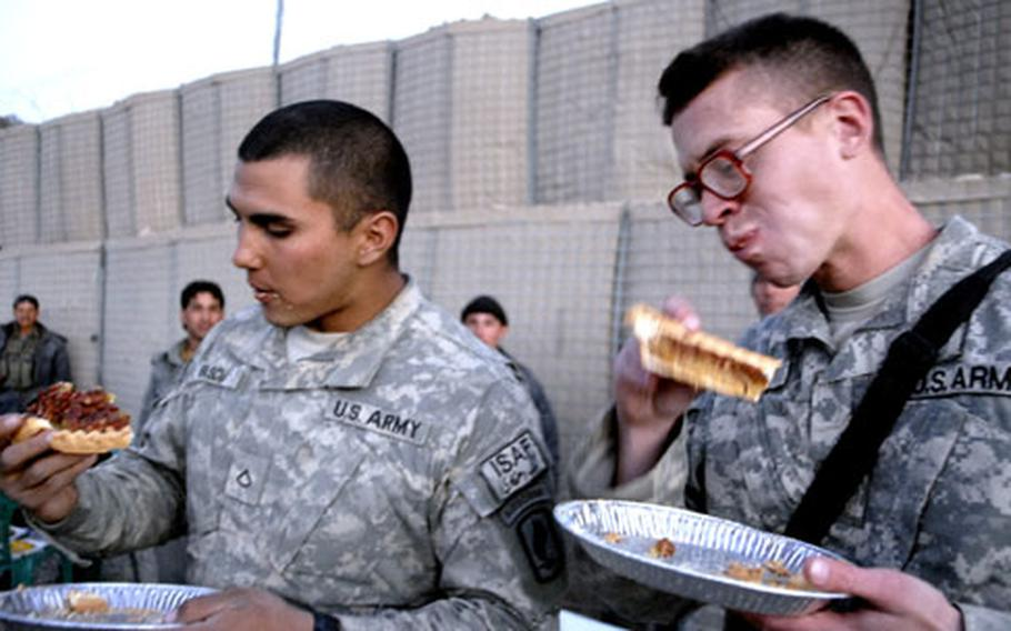 Soldiers with the 173rd Airborne Brigade (left) and 82nd Airborne Division (right) shovel pecan pie into their mouths during an impromptu eating contest in Paktika province on Thanksgiving in Afghanistan. The 82nd won.