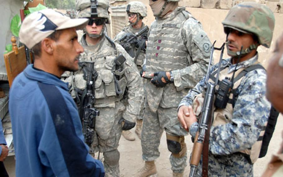 First Platoon, Company F, 2nd Squadron, 2nd Cavalry (Stryker) Regiment leader 1st Lt. Robert Johnston, 22, of Seattle, Wash. (second from left) and an Iraqi National Police officer (right) talk to Saha residents about essential services in their neighborhood on Tuesday.