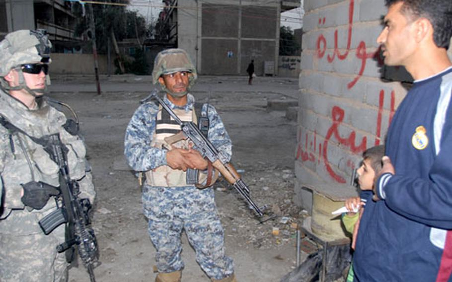 First Platoon, Company F, 2nd Squadron, 2nd Cavalry (Stryker) Regiment leader 1st Lt. Robert Johnston, 22, of Seattle, Wash. (left) and an Iraqi National Police officer talk to Saha residents about essential services in their neighborhood on Tuesday.