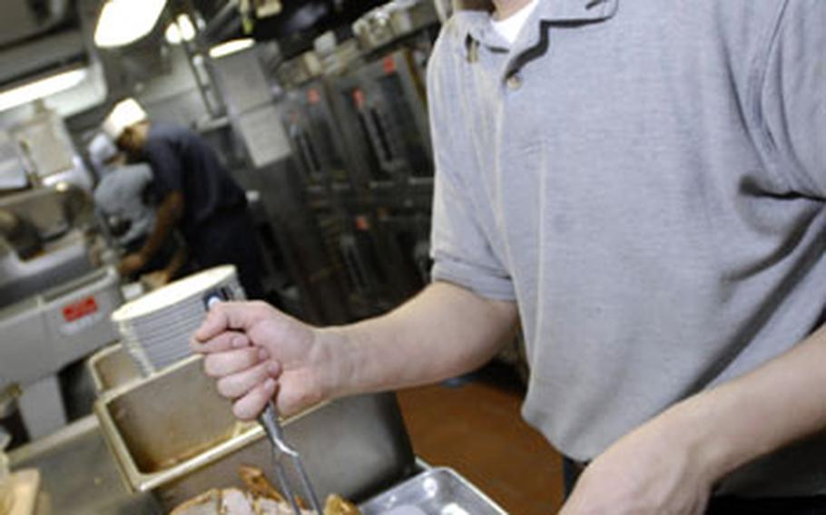 Petty Officer 3rd Class Borey By, 22, of Altaloma, Calif., slices turkey Thursday for Thanksgiving dinner on the USS Kitty Hawk. The carrier was scheduled to make a four-day stop in Hong Kong for the holiday, but the Chinese government denied the Kitty Hawk and other Navy vessels entry.