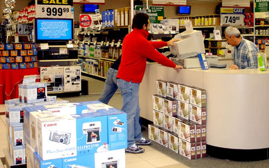 Workers at the Navy Exchange in Naples make last-minute preparations for the hundreds of customers who filed into the store for the start of the holiday shopping season.