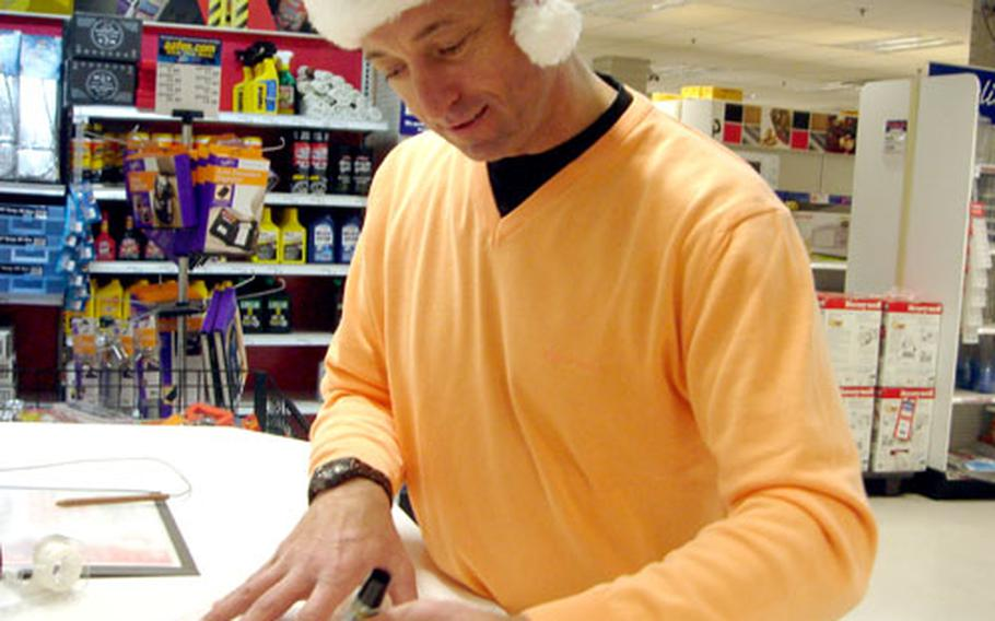 Senior Master Sgt. Mark Knapp, with U.S. Air Forces in Europe headquarters at Ramstein Air Base, makes an impromptu sign for a gift-wrapping booth he helped man Friday at the Vogelweh BX in Kaiserslautern, Germany. Knapp got some holiday shopping done before and after he volunteered.