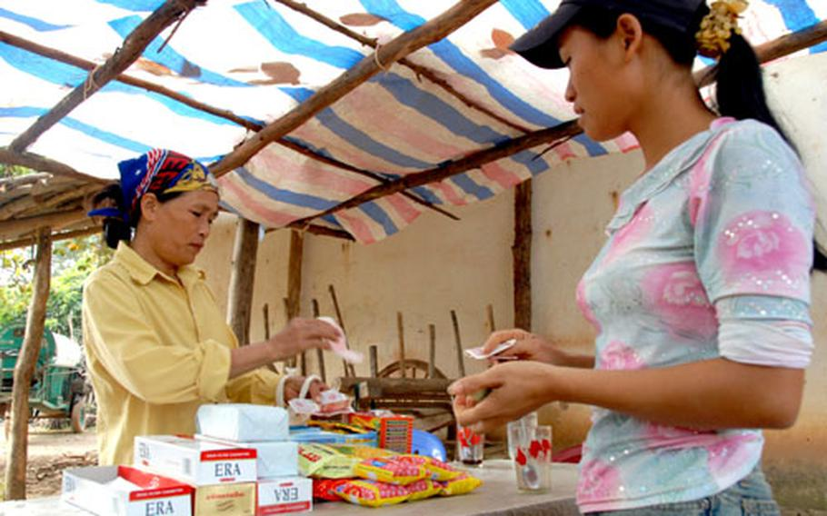 A Vietnamese worker pays for a glass of tea at an outdoor store, set up just outside the JPAC dig site. Many of the 90 Vietnamese hired to help with the dig, and the 17-member JPAC team, bought snacks and drinks from the vendor during their hourly breaks.