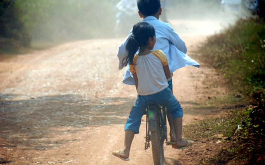 Two children ride on a bike on the bumpy dirt road leading to a JPAC dig site in rural Vietnam.