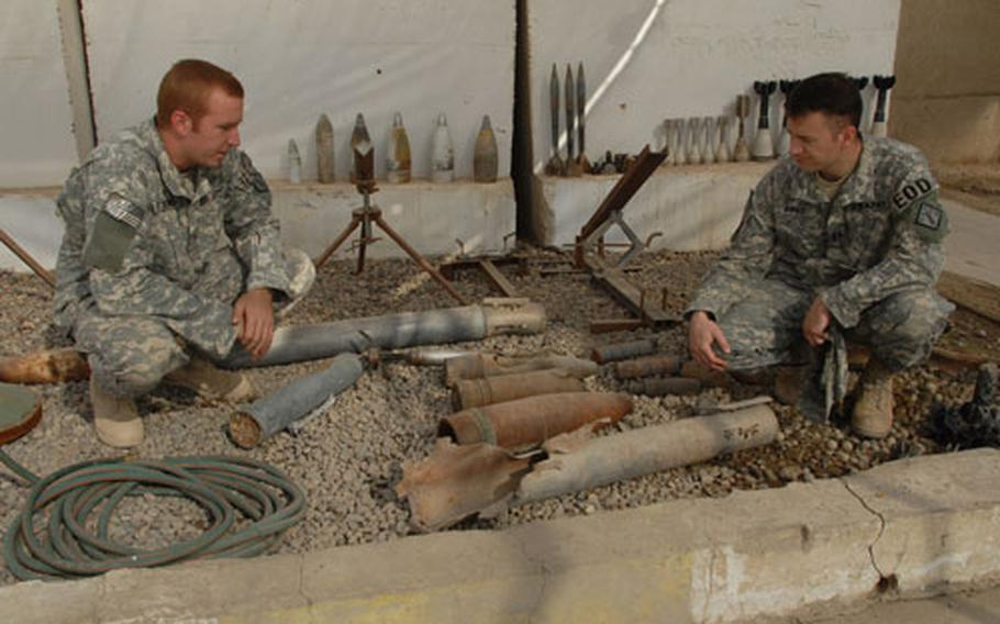 From left, First Lt. Dan Pitchford, 25, of Dassel, Minn. and Capt. David Ihrke, 32, of Houston, both members of the 47th Explosive Ordinance Disposal Company, show off their collection of seized enemy weaponry, including homemade grenades and a homemade rocket launcher, just left of Ihrke, at Camp Falcon, Baghdad.