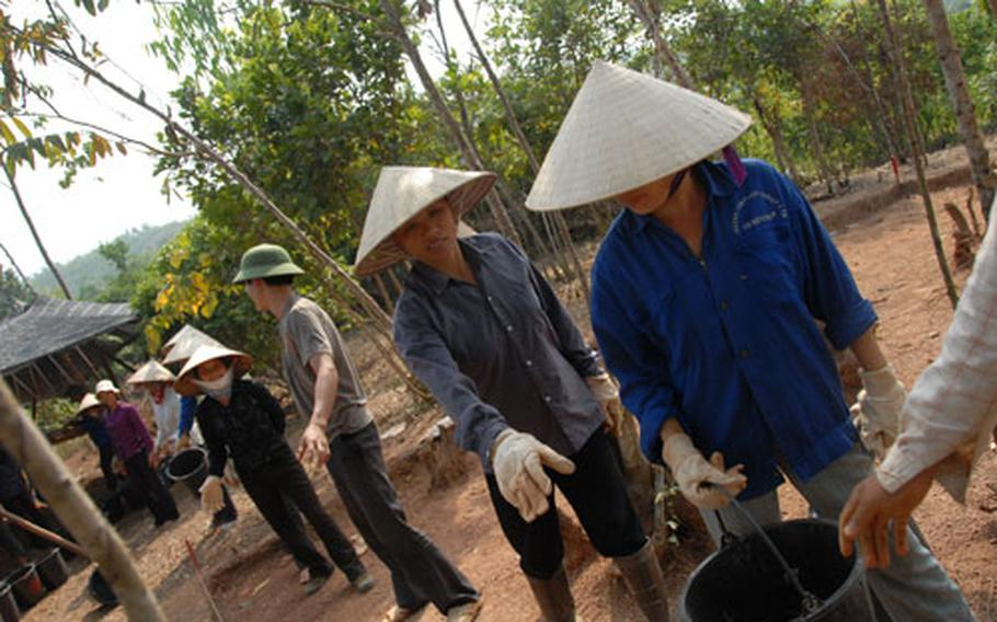 Vietnamese workers pass buckets of dirt from a hilltop dig site to a sifting station, where they and JPAC team members will look for bones and teeth in the dirt.