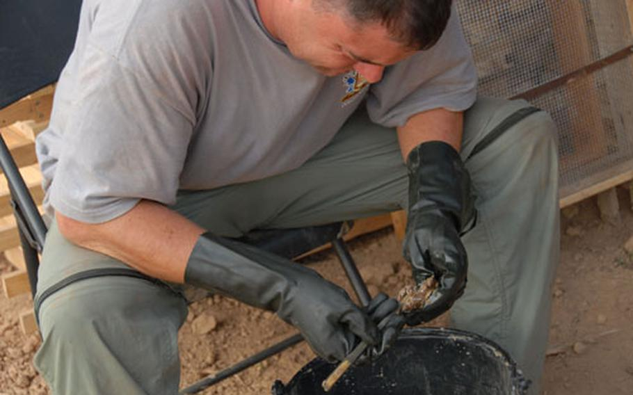 >At the end of a day of digging, Master Sgt. Scott Riker examines debris the JPAC team found after a day of digging in Vietnam. Riker is a life support investigator who can identify what kind of debris the team finds.