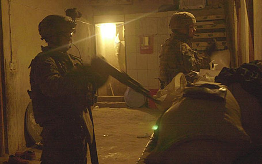 Soldiers from Baker Company, 1st Battalion, 15th Infantry Regiment catalog weapons and documents seized along with 13 suspected insurgents during an early-morning raid southeast of Baghdad.