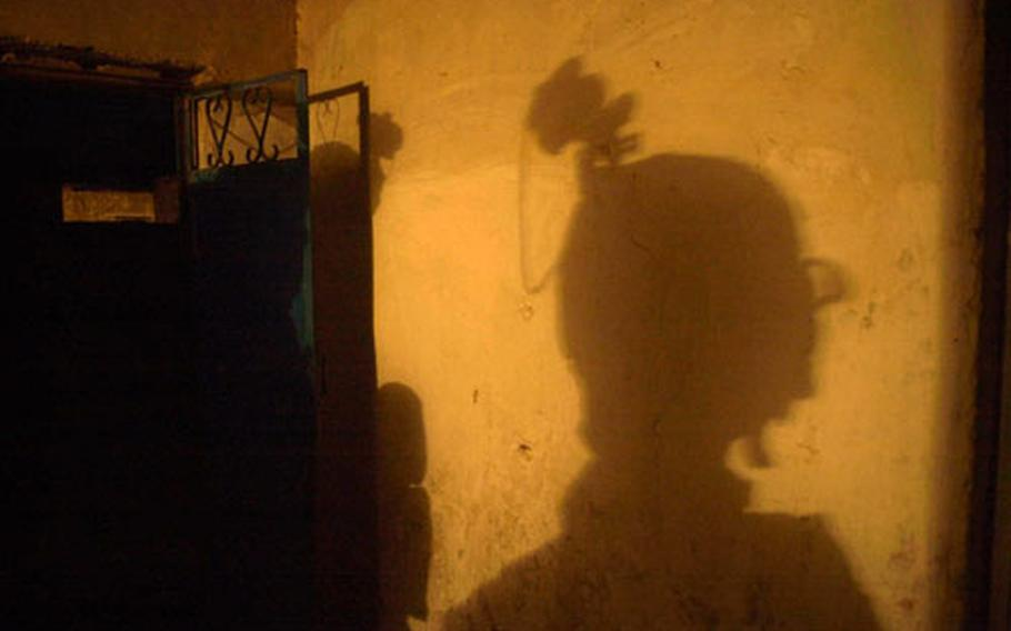 A soldier's shadow falls on the wall of a compound searched during an early-morning air assault mission near Salman Pak, Iraq.