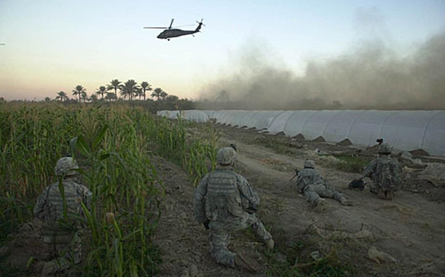 Soldiers wait as a Black Hawk helicopter lands to take the troops and 13 detainees back to base after the raid.