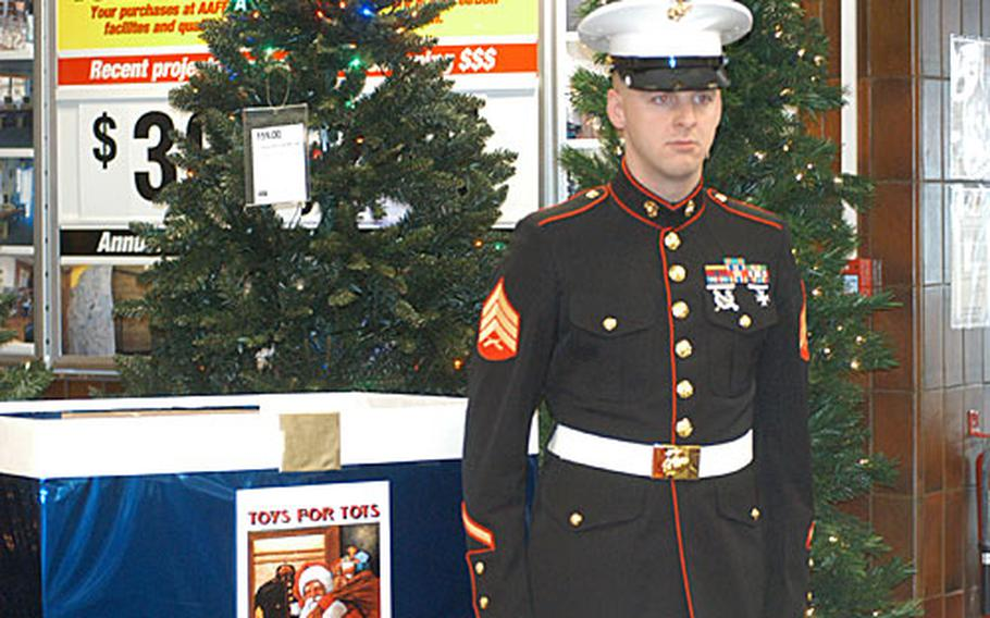Marine Sgt. Chris Greene stands next to a Toys for Tots donation box on RAF Alconbury. The Marines from the RAF Molesworth Joint Analysis Center are conducting the annual toy drive in England through Dec. 9.