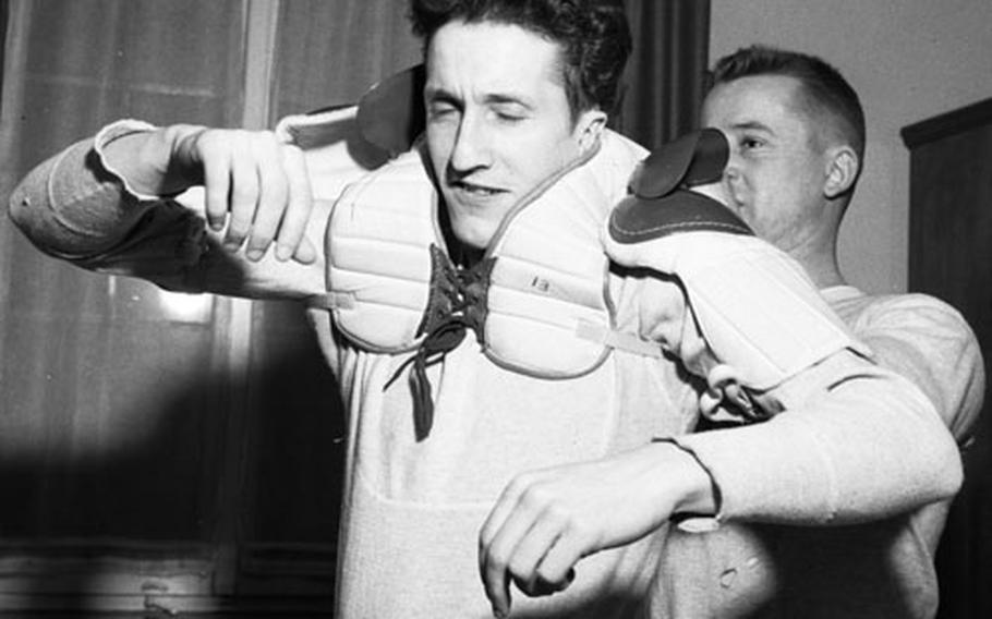 Vic Osowetski helps Ron O'Meara put on his pads before they leave for a game.