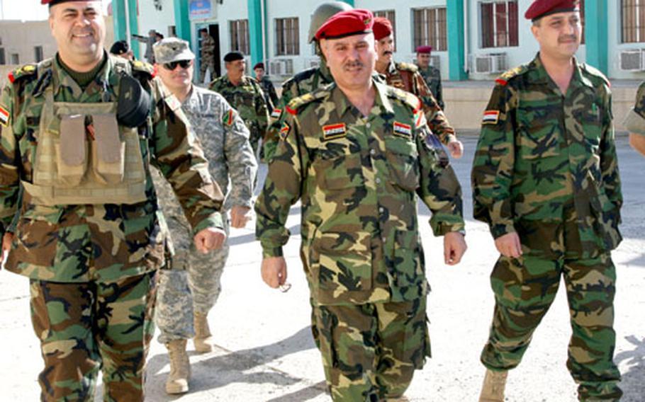 Iraqi Brig. Gen. Abdul-Jabar Saleh, center, talks with 4th Iraqi Army Division commander, Maj. Gen. Salahdin Mustafa Kamal, left, Tuesday after Saleh was replaced as commander of 1st Brigade, 4th Iraqi Army Division. Saleh was replaced by Brig. Gen. Mu'ayed Noradin, right.