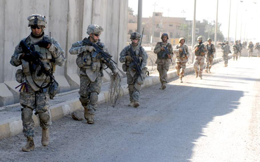 Company E soldiers and Iraqi Army troops patrol in front of Combat Outpost Blackfoot on Thursday.