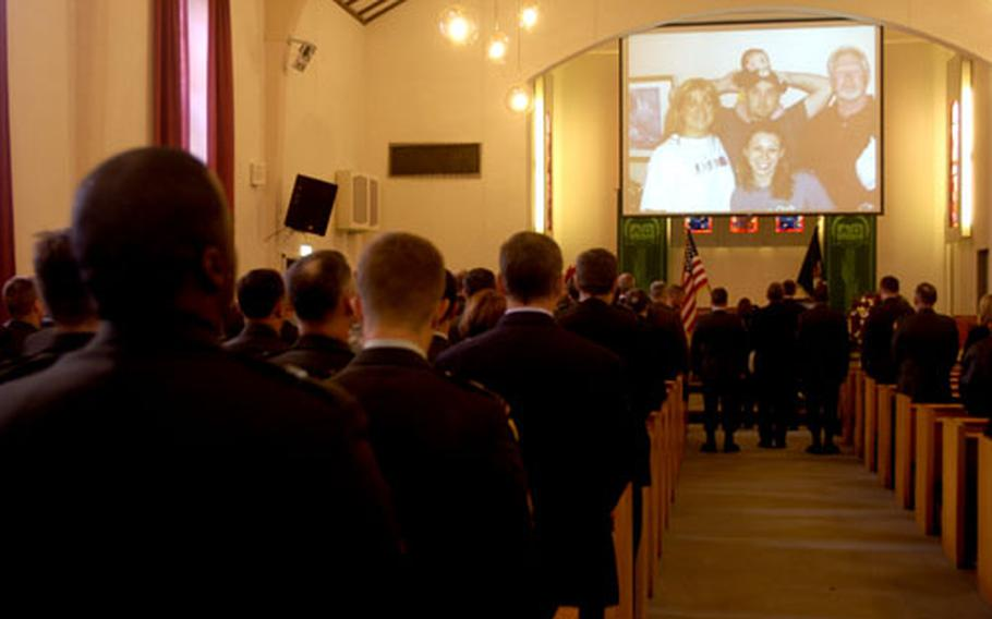 Mourners inside Panzer Chapel on Panzer Casern in Boblingen, Germany, watch a video tribute to Staff Sgt. Patrick F. Kutschbach of Company B, 1st Battalion, 10th Special Forces Group.