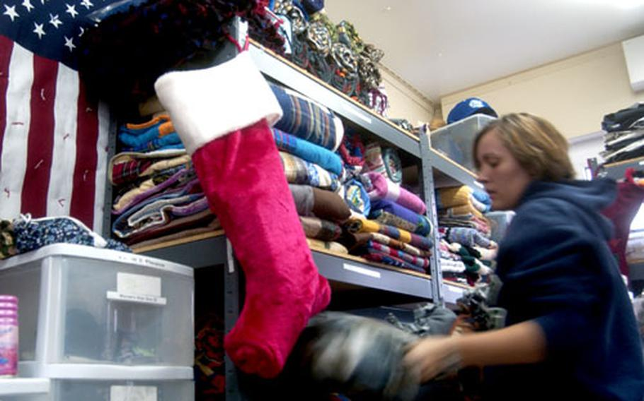 Jenny Clinton, a volunteer at Landstuhl's Wounded Warrior Ministry Center, stacks the shelves Tuesday as the center begins to receive its annual holiday surge of donations.