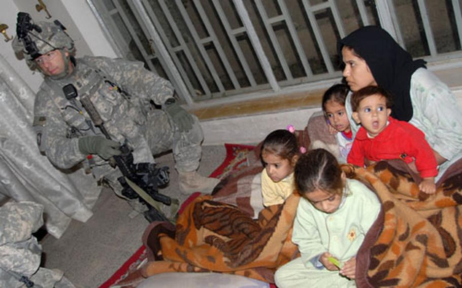 Company E, 2nd Squadron, 2nd Cavalry Regiment's 1st Sgt. Eric Geressy comforts a woman and four children after soldiers raided their house in search of alleged al-Qaida in Iraq member Abu Raquyyah early Monday morning.