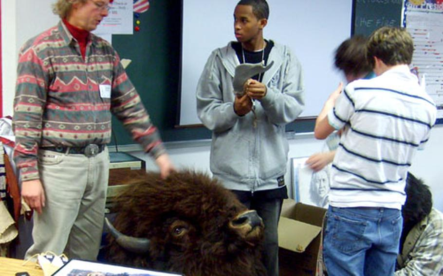 Peter Heiser lets students of a U.S. Minority Studies class look at American Indian artifacts, including a stuffed buffalo head, tomahawks and smoking pipe.