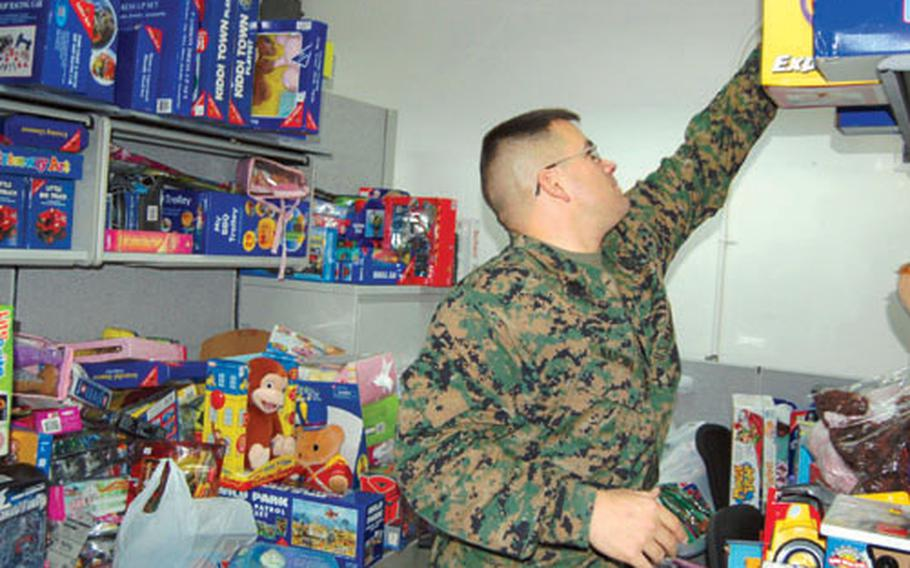 Staff Sgt. Nathan Natchke puts a toy on a shelf in a small cubicle at the Marine Forces Korea headquarters building on Yongsan Garrison, South Korea. Natchke said he's collected about 500 toys — one-tenth of what he'll need by Dec. 18.