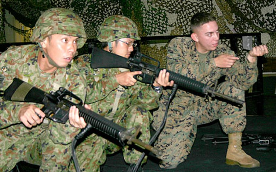 Lance Cpl. James Troupe, right, from Los Lunas, N.M., a marksmanship coach with 3rd Marine Logistics Group, demonstrates a firing position for Japan Ground Self-Defense Force troops at the Camp Kinser Indoor Simulator Marksmanship Trainer facility Wednesday.